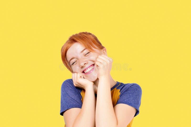有满意的表情的美丽的红发少妇,隔绝在黄色背景 有自然的可爱的女性关于 免版税库存照片