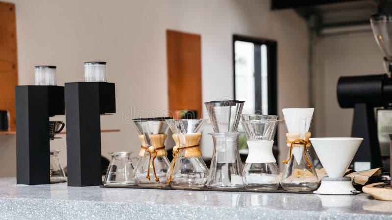 有滴水咖啡杯、滴水纸和煮浓咖啡器的各种各样的大小的咖啡设备在大理石顶面柜台 图库摄影