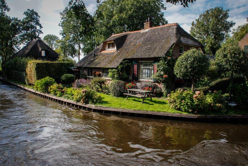 有漂浮小船和舒适传统房子的渠道的美丽的神仙的村庄 免版税库存图片