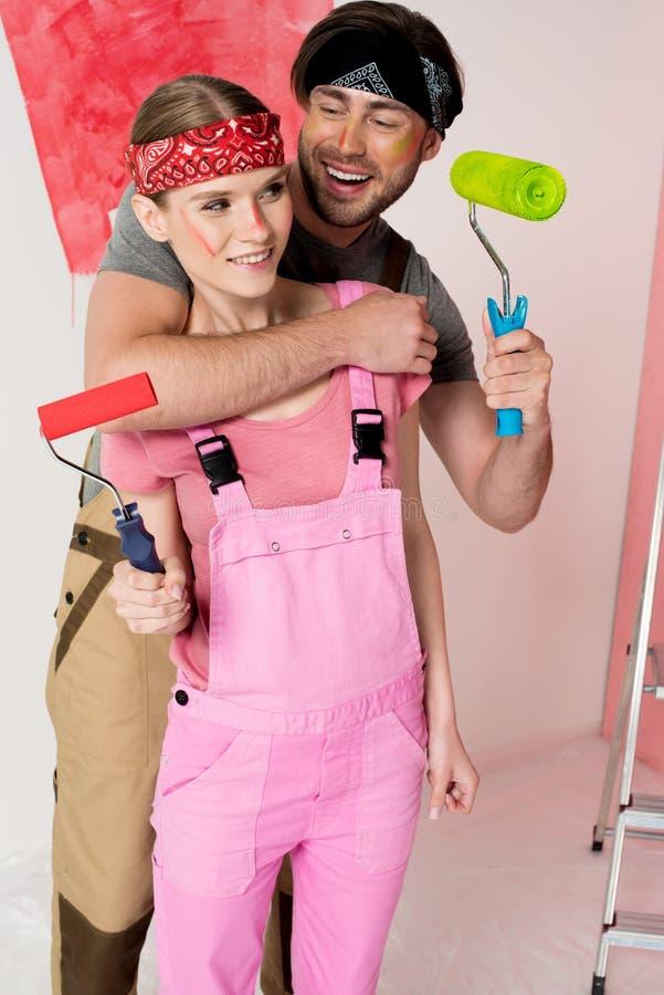 有漆滚筒拥抱的女朋友的微笑的人 图库摄影