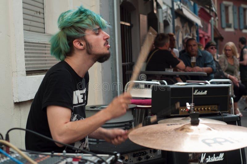 有演奏在一个摇滚乐队的蓝色头发的传神音乐家鼓在街道上在酒吧大阳台附近在免费活动期间 图库摄影