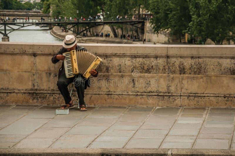 有演奏在桥梁的帽子的老人手风琴在多云天空的塞纳河在巴黎 免版税库存照片