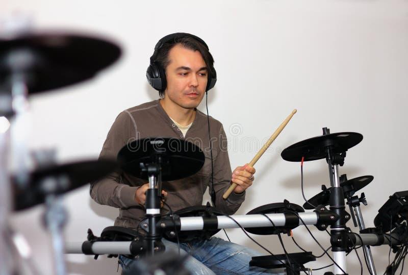 有演奏在a的耳机的英俊的鼓手电子鼓 库存图片