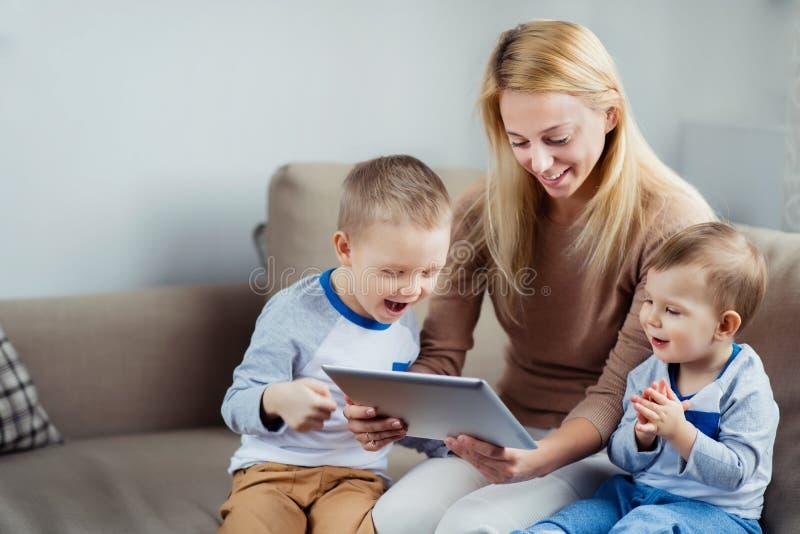 有演奏数字式片剂的两个儿子的母亲 免版税图库摄影