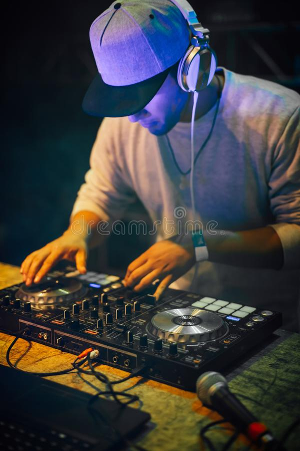有演奏混合的音乐的耳机的DJ在夜党 乐趣、青年、娱乐和费斯特概念 库存照片
