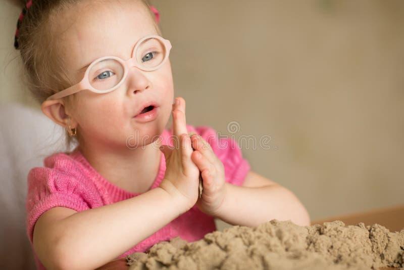 有演奏运动沙子的唐氏综合症的女孩 库存图片