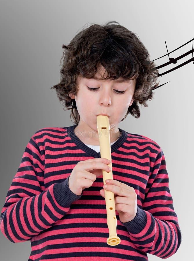 有演奏长笛的桃红色球衣的逗人喜爱的孩子 库存图片