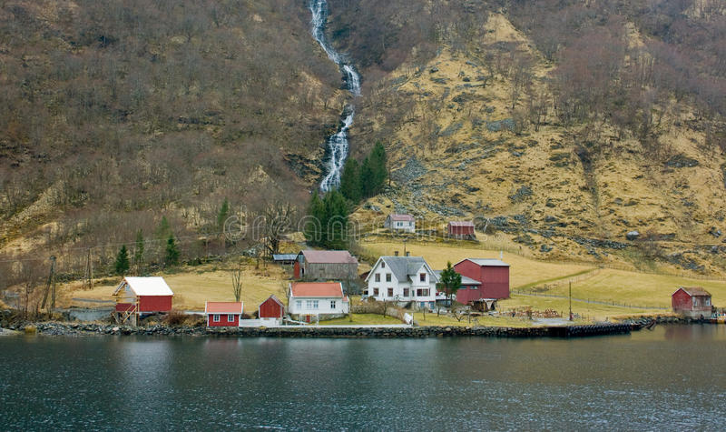 有瀑布的村庄在峡湾,挪威 斯堪的那维亚 库存照片