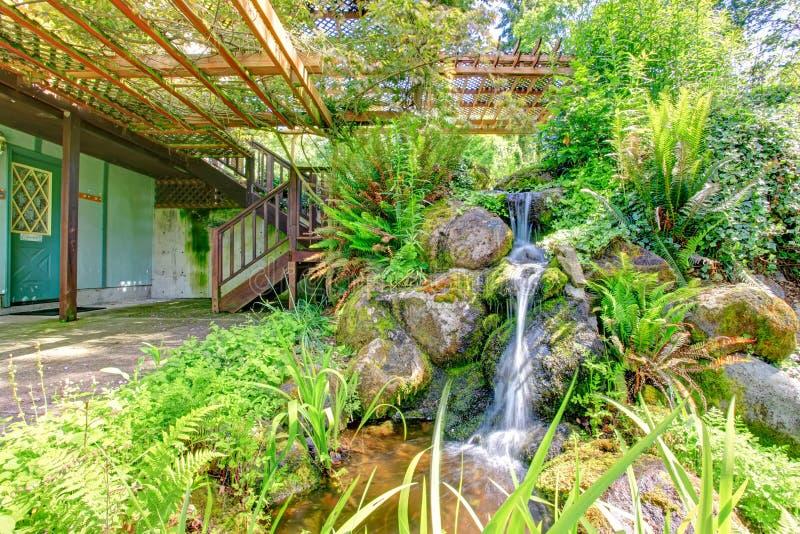 有瀑布的美丽的狂放的样式池塘。农厂房子后院 免版税库存图片