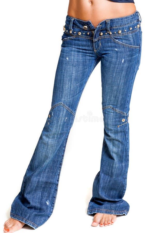有火光的时兴的牛仔裤在苗条妇女腿 免版税图库摄影