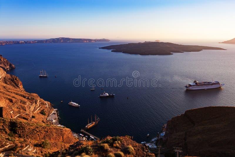 有火山的卡美尼岛和游轮的圣托里尼海 免版税图库摄影