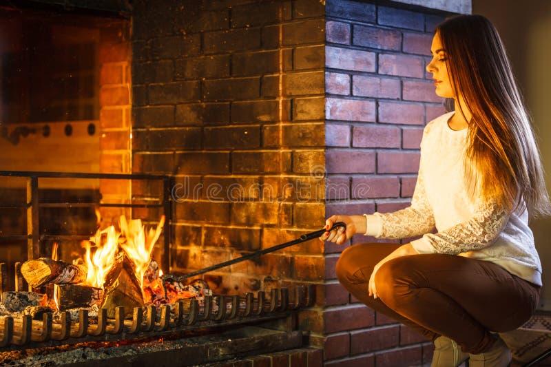 有火炉用具啤牌在家壁炉的妇女 库存照片