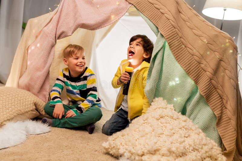 有火炬光的愉快的男孩在孩子帐篷在家 库存图片