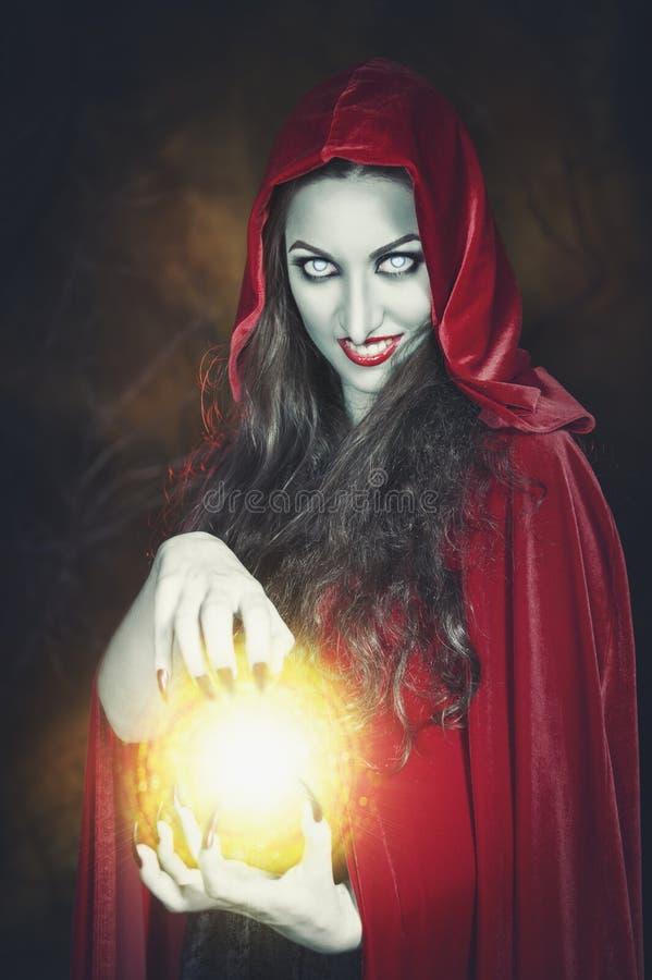有火球的万圣夜巫婆在她的手上 免版税库存图片