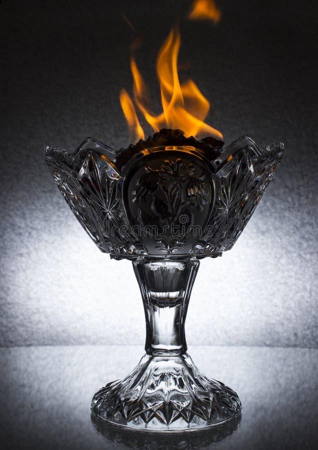 有火的一个大水晶花瓶在上面在玻璃桌上站立 免版税库存照片