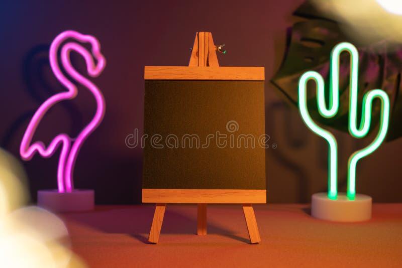 有火鸟和仙人掌霓虹桃红色和蓝色光的夏天黑板在桌上 增加的文本假装模板 免版税库存照片