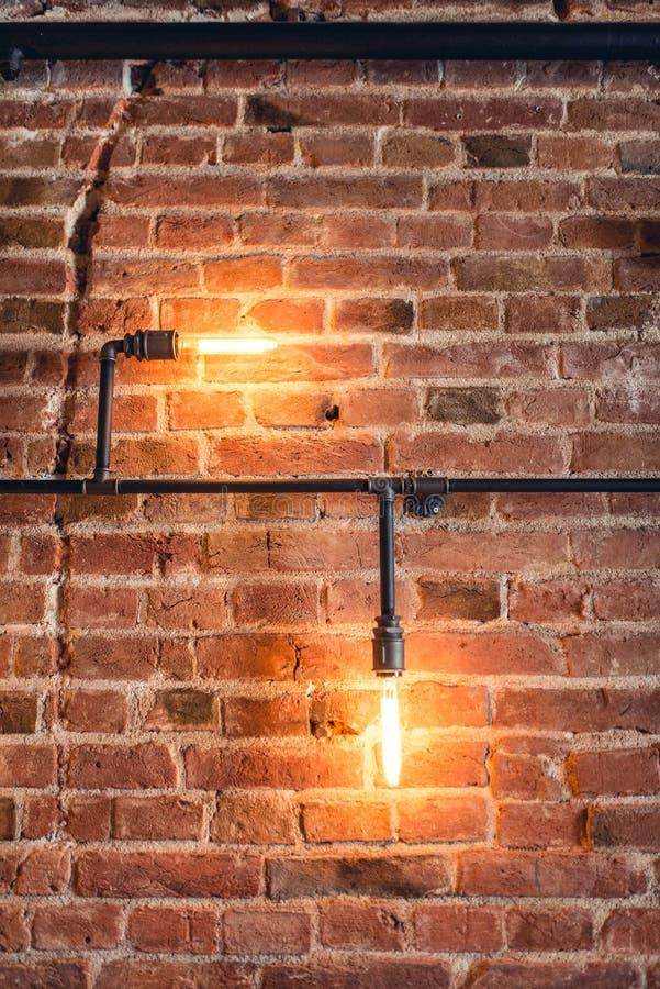 有灯、管子和砖的装饰墙壁 看老和葡萄酒墙壁,室内设计的 免版税库存图片