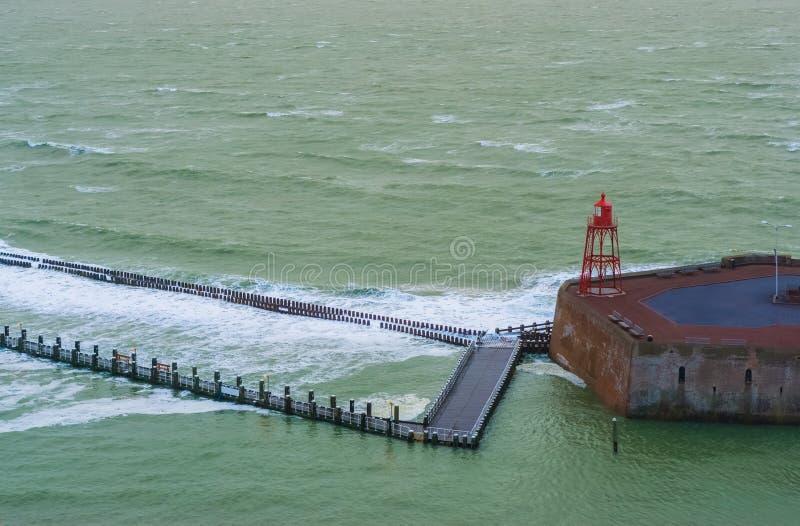 有灯塔和狂放的海,海风景的,弗利辛恩,西兰省,荷兰码头跳船 图库摄影