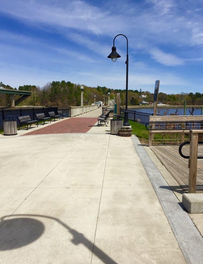 有灯杆的木板走道和阴影和小船在港口 库存照片