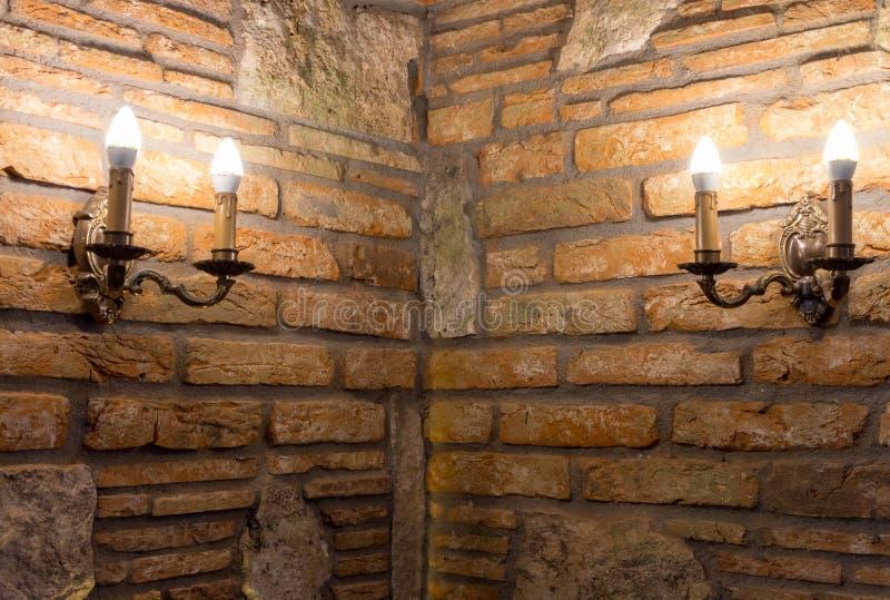 有灯的两个烛台在砖墙的角落在古老大厦的 中世纪内部 石头和砖老房子 免版税库存图片