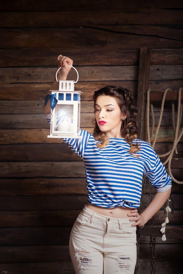 有灯笼的水手妇女在木背景 光 库存照片