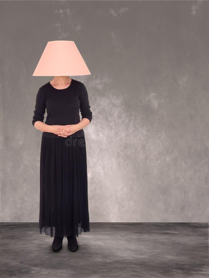 有灯罩的妇女在头 无形,一部分的家具 免版税库存照片