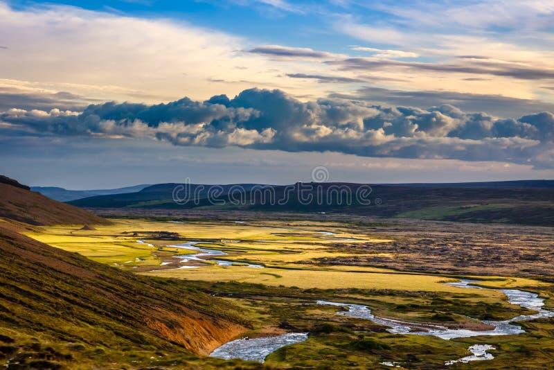 有灰色云彩的,绿色领域,小山a冰岛农村全景 库存图片