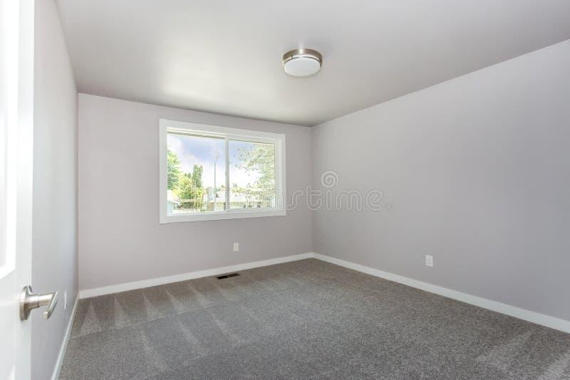 有灰色地毯地板的小空的室 库存图片