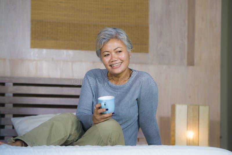 有灰色头发的可爱和成功的成熟妇女坐床饮用的咖啡放松了微笑愉快作为中间年迈的女性 免版税库存图片