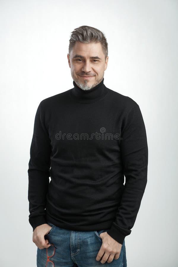 有灰色头发的愉快的更老的人在套头衫微笑 免版税库存照片
