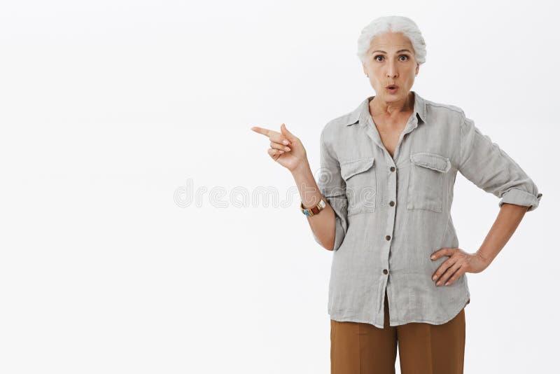 有灰色头发的被吸引的老婆婆在腰部指向的偶然宽松衬衣藏品手上留下好奇地折叠的嘴唇从 图库摄影
