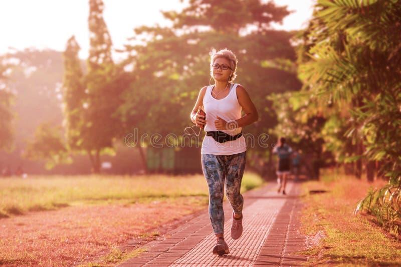 有灰色头发训练的中间年迈的40s或50s愉快和可爱的妇女在有绿色树的城市公园在做赛跑的日出 免版税图库摄影
