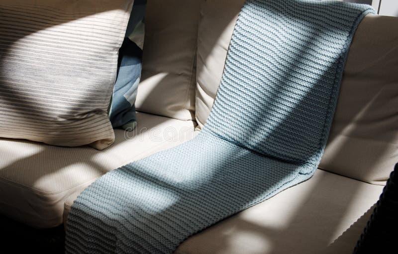 有灰色格子花呢披肩和枕头的米黄沙发 免版税库存图片
