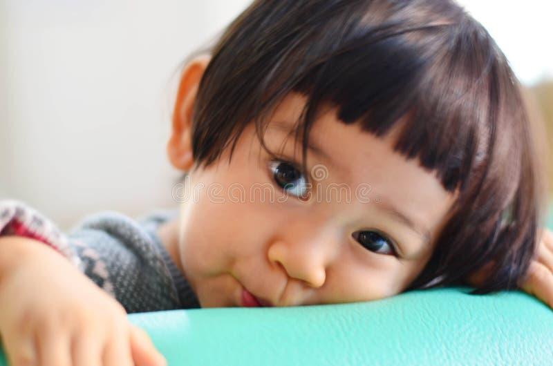 有灰色毛线衣的逗人喜爱的亚裔女婴看照相机, sel 免版税库存图片