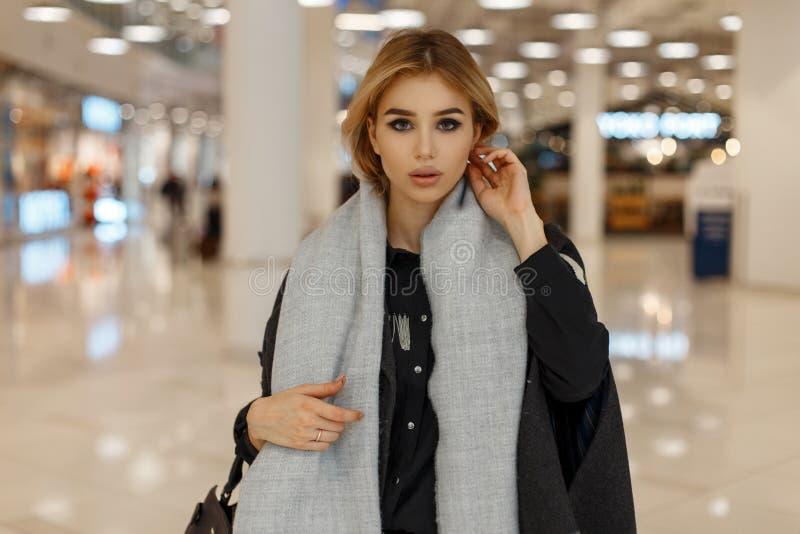 有灰色眼睛的性感的俏丽的时髦的年轻白肤金发的妇女在有葡萄酒围巾的一件豪华灰色外套有一个时兴的袋子的 图库摄影