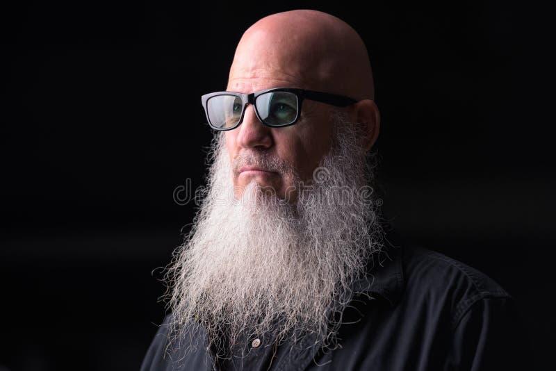 有灰色胡子的认为户外在晚上的秃头人画象  图库摄影