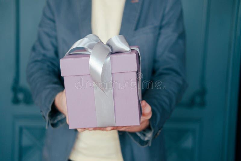 有灰色银色丝带的礼物盒在一个典雅的人的手上蓝色背景的 库存图片