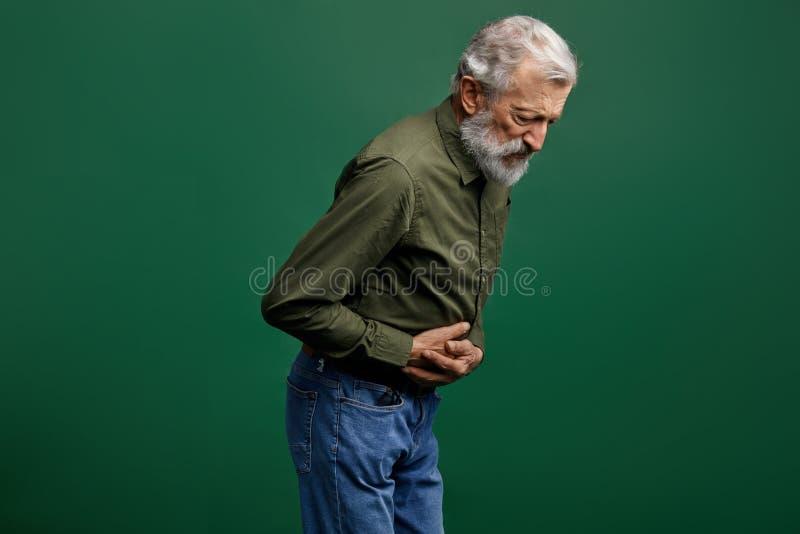 有灰色长的胡子的老人有胃的问题 免版税库存照片