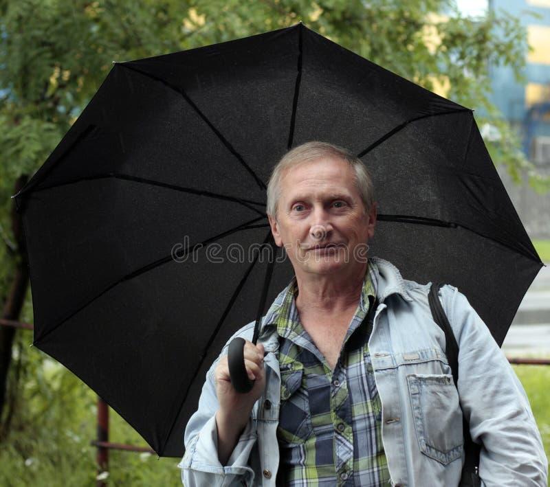 有灰色头发的严肃的人在黑伞下 免版税库存图片