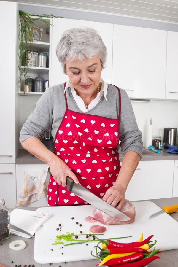 有灰色头发的资深或老妇人烹调在厨房里的。 免版税库存图片