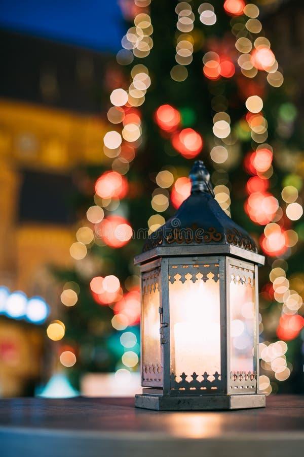 有灼烧的蜡烛的圣诞节灯笼在明亮的被弄脏的圣诞节 免版税库存照片
