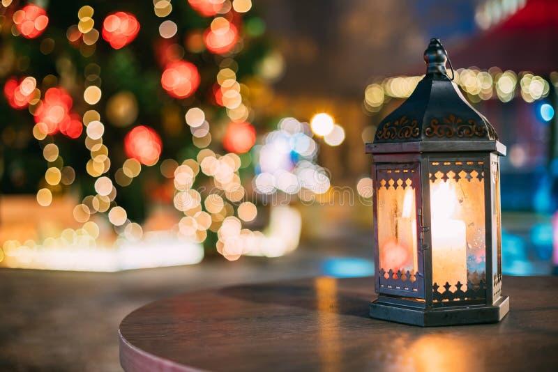 有灼烧的蜡烛的圣诞节灯笼在明亮的被弄脏的圣诞节 库存照片