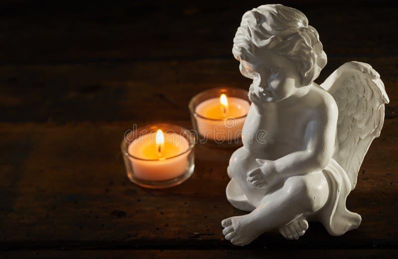 有灼烧的蜡烛的天使小雕象 图库摄影