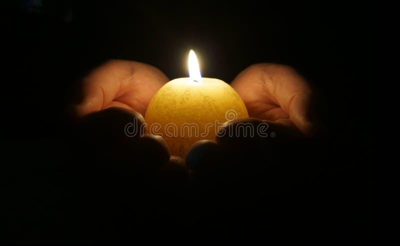 有灼烧的蜡烛的杯形手 免版税库存图片