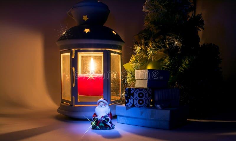 有灼烧的蜡烛的灯笼和与圣诞老人和礼物盒的圣诞树有阴影的 免版税库存图片