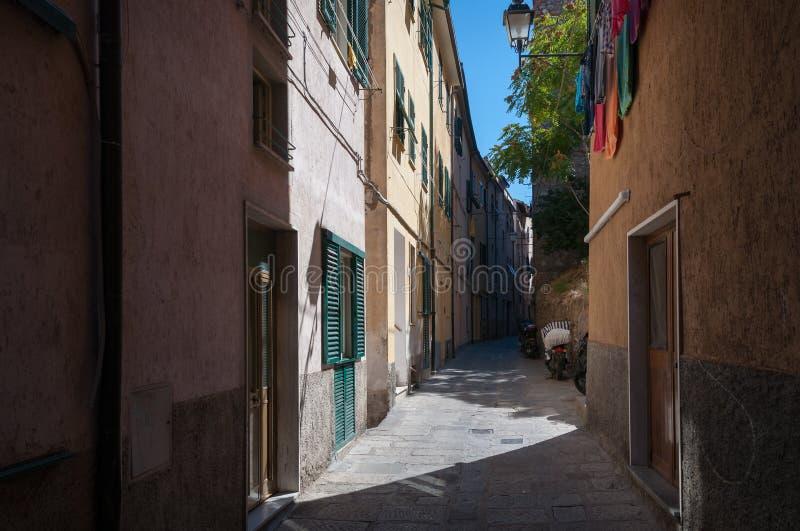 有烘干在晾衣绳的滑行车停放的和衣裳的狭窄的欧洲街道 库存照片