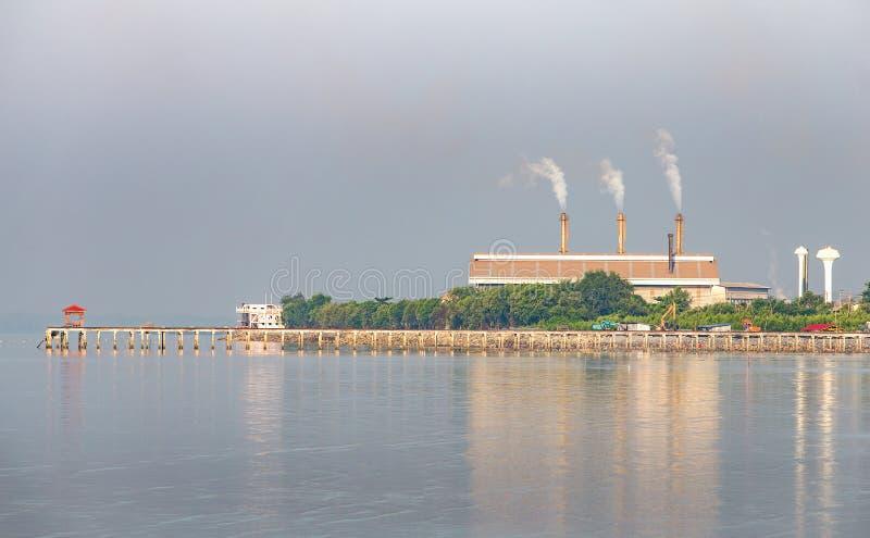 有烟的工厂在海滩附近 库存照片