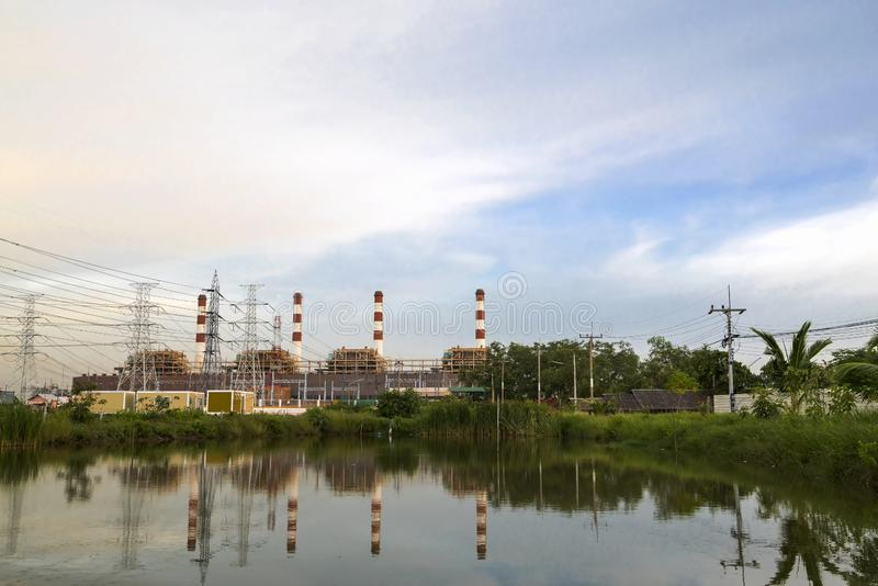 有烟窗的天然气电力设备和许多在chonburi泰国的杆与近水反射和美丽的天空 免版税库存照片