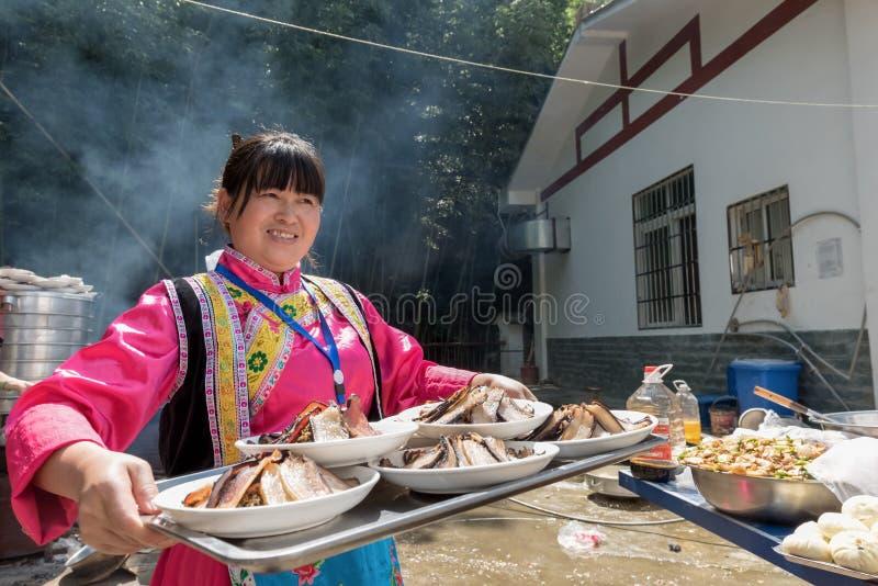 有烟肉盛肉盘的羌族女服务员  图库摄影