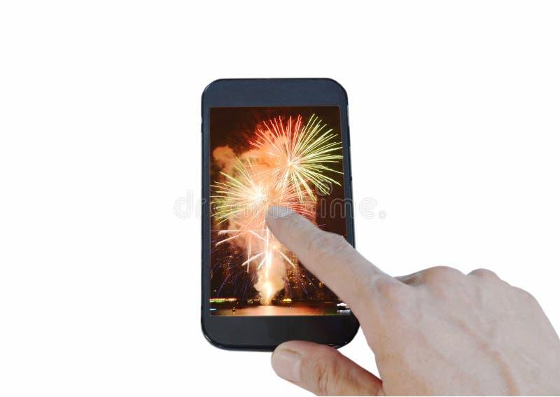 有烟花的人的指点手机屏幕在白色背景 免版税库存图片